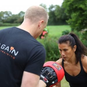 personal trainer personal training a client with boxing using boxing pads and gloves for fitness circuit class